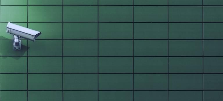 Überwachungskamera montiert an eine grüne Wand.