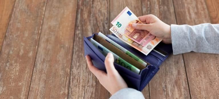 Frauenhände sortieren Geldscheine in einer Geldbörse.