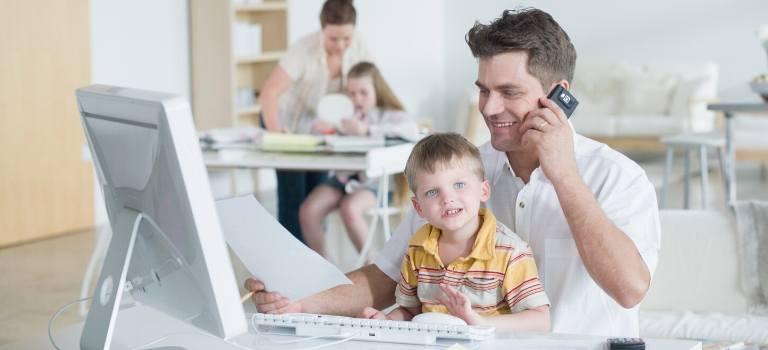 Ein Mann sitzt an einem Schreibtisch mit einem kleinen Jungen auf dem Schoß.