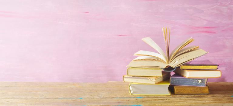 Ein Stapel Bücher vor einem rosa Hintergrund.