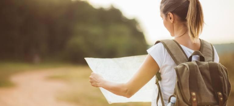Eine Frau schaut bei einer Wanderung auf eine Landkarte.