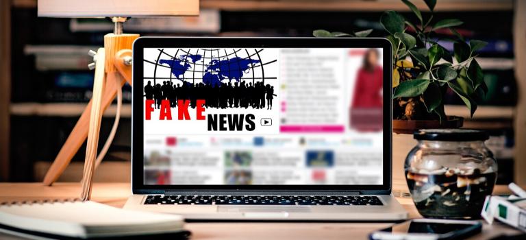 """Auf einem Laptop-Bildschirm steht der Begriff """"Fake News"""" geschrieben."""