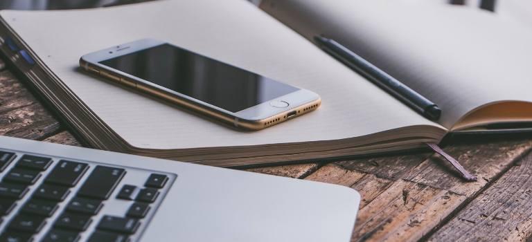Ein iPhone liegt auf einem geöffneten Buch, daneben ein Laptop.