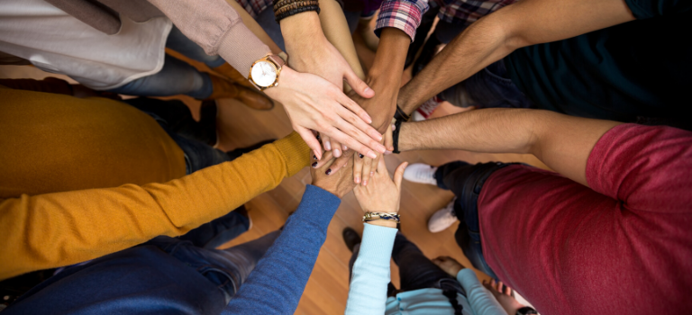 Mehrere Personen halten ihre Hände übereinander.