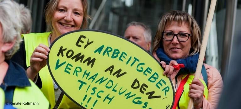 Zwei Frauen halten bei einem Streik von ver.di ein Schild.
