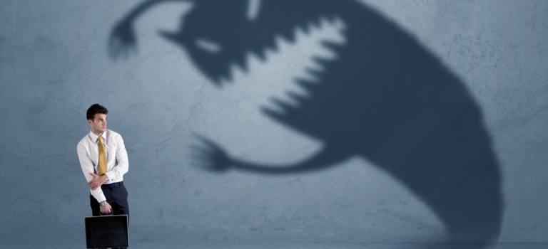 Das Bild zeigt einen Mann in Anzug mit Aktentasche, der vom Schatten eines Monsters angegriffen wird.