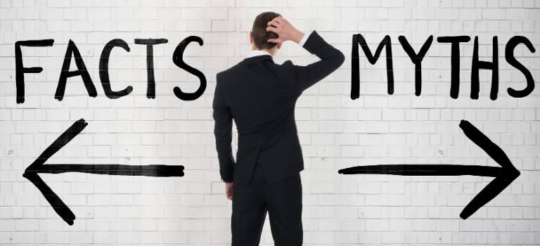 """Das Foto zeigt die Rückansicht eines Mannes in schwarzem Anzug, der sich den Kopf kratzt. Nach links zeigt ein Pfeil """"Facts"""", nach rechts zeigt ein Pfeil """"Myths""""."""
