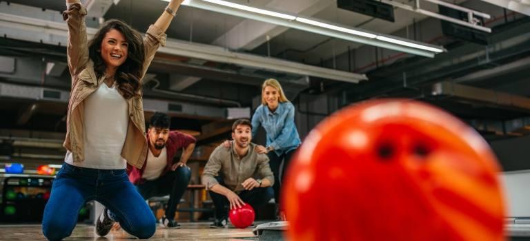 Das Foto zeigt eine froh mit vor Freude erhobenen Armen. Im Vordergrund eine Bowling-Kugel.