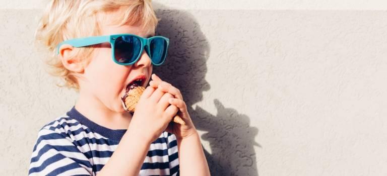 Ein blonder Junge leckt an einem Eis.