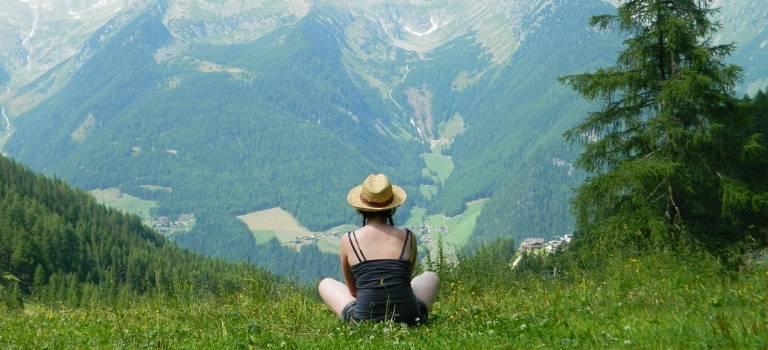 Ein Frau sitzt auf einer Wiese mit dem Rücken zur Betrachter*in vor Alpenkulisse.