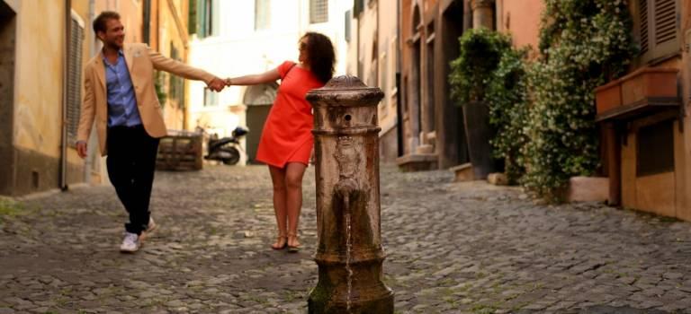 EIn Frau und ein Mann gehen Händchen haltend durch eine mediterrane Altstadt.