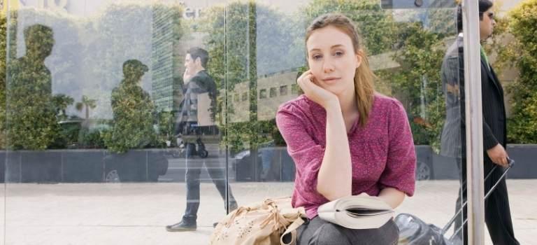 Eine Frau wartet an einer Haltestelle.
