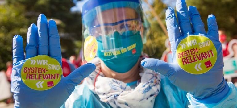 Eine Beschäftigte demonstriert mit Mundschutz und Visier.