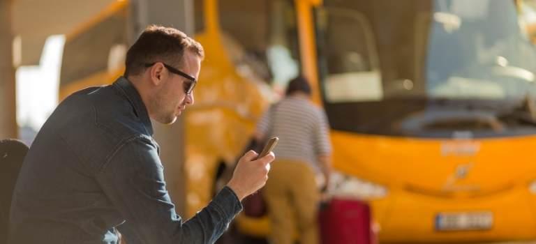EIn Mann an einer Bushaltestelle schaut auf sein Smartphone.