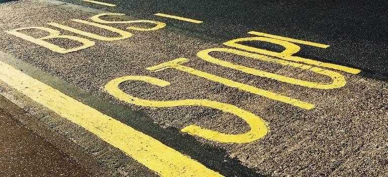 """Die Worte """"Bus Stop"""" in gelb auf einer Fahrbahn."""