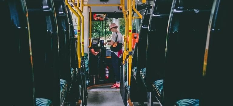 Eine Frau kauft eine Fahrkarte beim Busfahrer.